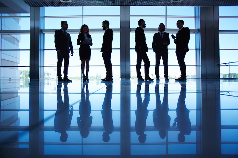Silhouettes of several office workers standing by the window and working